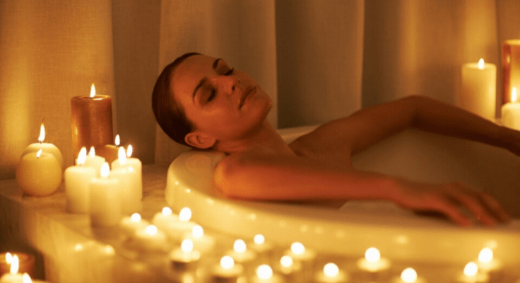 relaxed woman taking a bath with candles arount